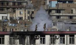 Un grupo de las fuerzas de seguridad corre sobre el techo de la sede de la policía de tráfico afgana tras un ataque en Kabul, ene 21 2013. Suicidas con bombas y hombres armados lanzaron el lunes un ataque de ocho horas contra la sede de la policía de tráfico afgana, informaron funcionarios de Kabul, en lo que es el segundo ataque coordinado contra un edificio del Gobierno en menos de una semana. REUTERS/Omar Sobhani