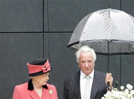 Michael Winner holds an umbrella as the Queen Elizabeth II looks on at the unveiling of the National Police Memorial in the Mall in London, April 26, 2005. REUTERS/Stephen Hird/Files