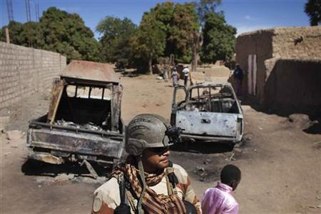 A French soldier stands guard in front of charred pickup trucks used by Islamist rebels in Diabaly January 21, 2013. French and Malian armoured columns rolled into the central Mali town of Diabaly on Monday after the al Qaeda-linked Islamist rebels who seized it a week ago melted into the bush to avoid air strikes. The pickup trucks were destroyed during fighting between the Malian army and rebels. REUTERS/Joe Penney (MALI - Tags: POLITICS MILITARY CIVIL UNREST CONFLICT)