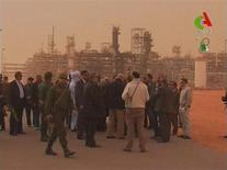 A delegation led by Algerian Oil Minister Youcef Yousfi and Japanese vice Foreign Affairs Minister Miuro Kiuchi visit the Tiguentourine Gas Plant, located about 50 km (30 miles) from the town of In Amenas in this still image from video footage taken on January 20, 2013. Japanese vice Foreign Affairs Minister Kiuchi led a delegation of Japanese officials to the Tiguentourine Gas Plant deep in the Sahara on Sunday, where at least 48 hostages were killed during the four-day siege. At least 10 Japanese are still missing in the plant which is operated by Britain's BP, Norway's Statoil and Algeria's state energy company. Japanese engineering firm JGC is one of the foreign companies operating in the plant which is close to the Libyan border. REUTERS/Canal Algerie via Reuters TV