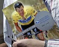 """Foto de arquivo onde homem carrega livro autografado pelo ciclista norte-americano Lance Armstrong, na França. Um """"trote"""" em uma biblioteca australiana, com um aviso declarando que os livros sobre Armstrong, que caiu em desgraça por doping, seriam colocados na seção de ficção, virou um sucesso na Internet. 13/06/2013 REUTERS/Robert Pratta"""