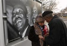 Casal é visto em frente a foto de Martin Luther King Jr. na fachada do Museu Nacional de História e Cultura Afro-Americana em Washington, em 2012. Os Estados Unidos honraram a memória de Luther King nesta segunda-feira realizando homenagens e cerimônias comemorativas, com multidões esperadas em eventos em Atlanta, cidade natal do líder de direitos civis assassinado. 22/02/2012 REUTERS/Kevin Lamarque