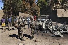 Columnas armadas de soldados franceses y malienses entraron el lunes en las localidades de Diabaly y Douentza, en el centro de Mali, después de que los rebeldes islamistas vinculados con Al Qaeda que tomaron la zona hace una semana escaparan para evitar los ataques aéreos. En la imagen, soldados franceses de pie ante los restos de camionetas utilizadas por rebeldes islamistas en Diabaly, el 21 de enero de 2013. REUTERS/Joe Penney