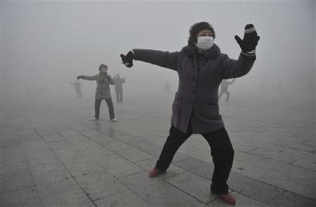 A woman wears a mask as she does her morning exercise outdoors in Fuyang, Anhui province, January 14, 2013. REUTERS/China Daily