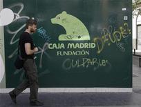 Las refundadas cajas de ahorros podrán ejercer el control de su actividad bancaria a través de fundaciones con la condición de que el Banco de España supervise la gestión financiera de estas sociedades, a las que se podrá exigir en algunos casos unos fondos de reservas, dijeron el lunes fuentes del Ministerio de Economía. En la imagen de archivo, un hombre pasa por delante de un cartel de la Fundación Caja Madrid, en el centro de Madrid, el 10 de mayo de 2012. REUTERS/Andrea Comas