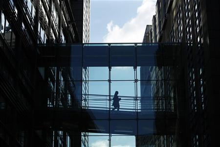 A woman crosses a walkway between Goldman Sachs offices in central London October 15, 2009. REUTERS/Luke MacGregor