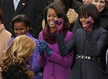 First Lady Michelle Obama (R) and her daughters Malia (C) and Sasha cheer as Beyonce returns to her seat after singing the Star Spangled Banner after the swearing-in of U.S. President Barack Obama in Washington, January 21, 2013. REUTERS/Kevin Lamarque