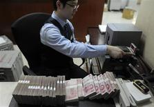 An employee counts 100 Chinese yuan banknotes at a bank in Hefei, Anhui province, January 21, 2013. Yield-chasing investors, whose hunger for income powered a long rally in Asian junk-rated bonds, are finally feeling the first symptoms of indigestion after a year-long binge. To match Analysis ASIA-MARKETS/CREDIT REUTERS/Stringer (CHINA - Tags: BUSINESS)