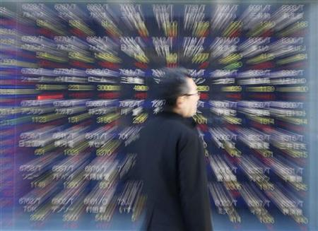 A man looks at a stock index board outside a brokerage in Tokyo January 18, 2013. REUTERS/Kim Kyung-Hoon