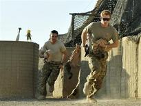 Britain's Prince Harry (R) races out from the VHR (very high ready-ness) tent with fellow crew, to scramble his Apache helicopter at Camp Bastion, southern Afghanistan in this photograph taken November 3, 2012, and released January 21, 2013. REUTERS/John Stillwell/Pool