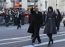 U.S. President Barack Obama and first lady Michelle Obama walk and wave after emerging from the presidential limousine during the inaugural parade from the Capitol to the White House in Washington, January 21, 2013. REUTERS/Larry Downing (UNITED STATES - Tags: POLITICS)