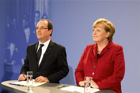 German Chancellor Angela Merkel and French President Francois Hollande speak during a meeting with some 200 German and French students and pupils as part of celebrations of the 50th anniversary of the Elysee Treaty, in the Chancellery in Berlin, January 21, 2013. REUTERS/Kay Nietfeld/Pool