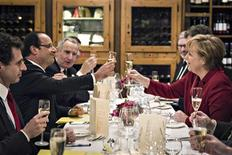 German Chancellor Angela Merkel (R) and French President Francois Hollande salute to each other during a private dinner in a Berlin restaurant at the eve of celebrations to mark the 50th anniversary of the Elysee Treaty, January 21, 2013. REUTERS/Jesco Denzel/Bundespresseamt/Pool