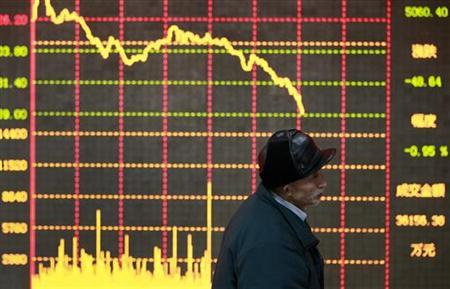 An investor stands in front of an electronic board showing stock information at a brokerage house in Huaibei, Anhui province January 11, 2013. REUTERS/Stringer