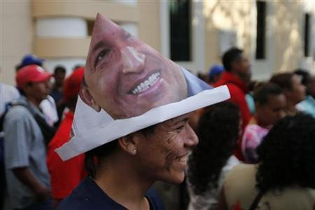 A supporter of Venezuela's President Hugo Chavez wears a hat with an image of President Hugo Chavez outside the national assembly, while vice president Nicolas Maduro delivers the state of nation, in Caracas January 15, 2013. REUTERS/Jorge Silva