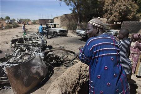 Diabaly residents look at charred pickup trucks destroyed by French airstrikes in Diabaly, Mali, January 21, 2013. REUTERS/Joe Penney (MALI - Tags: CIVIL UNREST POLITICS CONFLICT)