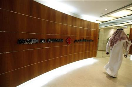 A man walks past a sign at the Majid Al Futtaim headquarters in Dubai during the Reuters Consumer and Retail Summit September 11, 2012. REUTERS/Jumana ElHeloueh