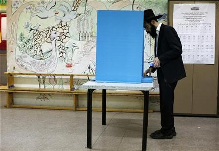 An ultra-Orthodox Jewish man stands near a booth at a polling station in the West Bank Jewish settlement of Kochav Ya'acov, north of Jerusalem, January 22, 2013. REUTERS/Baz Ratner (WEST BANK - Tags: POLITICS ELECTIONS)