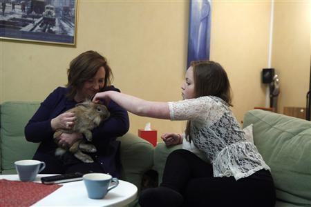 Emelie Olsson (R) and her mother Marie play with rabbit Stampe in Stockholm January 19, 2013. REUTERS/Ints Kalnins