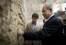 Los israelíes acudían el martes a votar en unas elecciones en las que se esperaba que el primer ministro Benjamin Netanyahu consiguiera una tercera victoria, llevando al estado judío más a la derecha, lejos de la paz con los palestinos y hacia la confrontación con Irán. En la imagen, Netanyahu deposita una nota en el Muro de las Lamentaciones de Jerusalén tras votar en las elecciones parlamentarias, el 22 de enero de 2013. REUTERS/Uriel Sinai/Pool