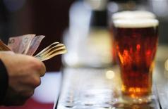 Посетитель бара в отеле Occidental Hotel в Сиднее платит за пиво, 21 июня 2011 года. Темпы роста объемов продаж пивоваренной компании SABMiller замедлились в третьем квартале из-за слабых показателей в Китае, переживающем сейчас самую холодную за последние 28 лет зиму. REUTERS/Tim Wimborne