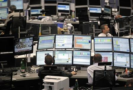 Traders work at their desks at the Frankfurt stock exchange July 24, 2012. REUTERS/Alex Domanski/Files