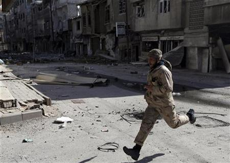 A fighter from the Sadik unit of Free Syrian Army's Tahrir al Sham brigade runs across a street during a heavy fighting in Mleha suburb of Damascus January 21, 2013. REUTERS/Goran Tomasevic