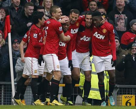 Manchester United's Patrice Evra (C) celebrates his goal against Liverpool with team mates during their English Premier League football match at Old Trafford in Manchester, northern England, January 13, 2013. REUTERS/Phil Noble