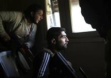 Rebeldes sírios se protegem durante combate com forças leais ao ditador Bashar al-Assad, próximo a Damasco. 21/01/2013. REUTERS/Goran Tomasevic