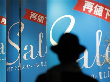 A man walks past sale signs at a shopping district in Tokyo January 22, 2013. REUTERS/Kim Kyung-Hoon