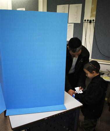 A boy helps his father place a ballot into an envelope at a polling station in the West Bank Jewish settlement of Kochav Ya'acov, north of Jerusalem January 22, 2013. REUTERS/Baz Ratner