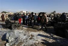 Residents gather at the site of a car bomb attack in the Shuala district in Baghdad, January 22, 2013. REUTERS/Mohammed Ameen
