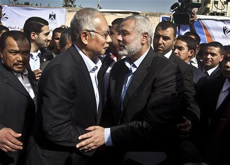 Malaysian Prime Minister Najib Razak (L) hugs senior Hamas leader Ismail Haniyeh during a cornerstone placing ceremony in Gaza City January 22, 2013. REUTERS/Ali Ali/Pool