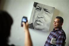 El convaleciente presidente de Venezuela, Hugo Chávez, está realizando un tratamiento de fisioterapia para poder volver a su país desde Cuba, donde permanece desde hace más de un mes tras una compleja cirugía por el cáncer que padece, dijo el martes su homólogo boliviano Evo Morales. En la imagen, un visitante posa junto a un cuadro retrato del presidente Hugo Chávez en una exposición en su honor en un edificio del gobierno en Caracas, el 17 de enero de 2013. REUTERS/Jorge Silva