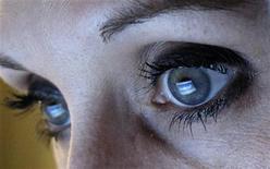 Ser testigo de las vacaciones, la vida amorosa y los éxitos laborales de los amigos en Facebook puede provocar envidia y despertar sentimientos de tristeza y soledad, según investigadores alemanes. En la imagen de archivo, un mujer observa la página web de Facebook, que se refleja en sus pupilas. REUTERS/Michael Dalder