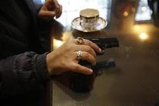 """Las mujeres en la capital de India están tomando clases de autodefensa, comprando sprays de pimienta, reservando taxis con mujeres conductoras o saliendo del trabajo antes, señales todas ellas de la creciente inseguridad tras la brutal violación múltiple y asesinato de una mujer el mes pasado. En la imagen, Nalini Bharatwaj, de 37 años, sostiene una pistola con sus manos para """"callar a cualquiera que intente molestarme"""", el 16 de enero en Nueva Delhi. REUTERS/Mansi Thapliyal"""