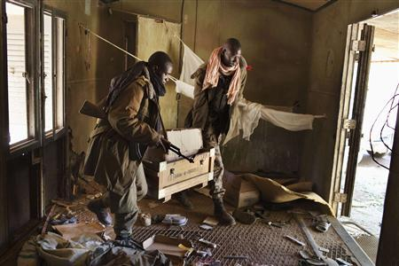 Malian soldiers carry a box of ammunition after searching through debris at a Malian military camp in Diabaly, Mali, January 21 2013. REUTERS/Joe Penney