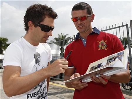 Marussia Formula One driver Timo Glock (L) of Germany signs an autograph as he arrives at the paddock ahead of the Malaysian F1 Grand Prix at Sepang International Circuit outside Kuala Lumpur March 22, 2012. REUTERS/Tim Chong/Files