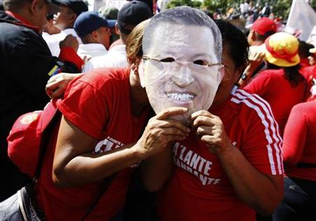 Supporters of Venezuelan President Hugo Chavez hold a mask depicting him while attending a rally in Caracas January 10, 2013. REUTERS/Edwin Montilva