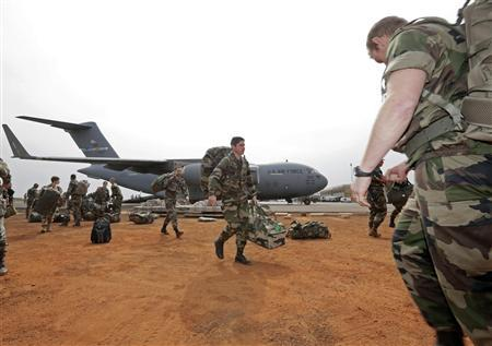 French soldiers carry their equipment after arriving on a US Air Force C-17 transport plane at the airport in Bamako January 22, 2013. The United States has started transporting French soldiers and equipment to Mali as part of its logistical aid to French forces fighting Islamist militants in the north of the country, a U.S. official said on Tuesday. REUTERS/Eric Gaillard (MALI - Tags: CIVIL UNREST CONFLICT MILITARY)