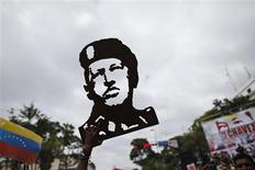 El presidente de Venezuela, Hugo Chávez, está realizando un tratamiento de fisioterapia para poder volver a su país desde Cuba, donde lleva un mes y medio recuperándose de la compleja operación de un cáncer que amenaza su permanencia en el poder, dijo el martes su homólogo boliviano Evo Morales. En la imagen de archivo, un seguidor del presidente venezolano Hugo Chávez sostiene una reproducción de madera de la silueta del mantario durante una concentración delante del Palacio de Miraflores en Caracas, el 10 de enero de 2013. REUTERS/Jorge Silva