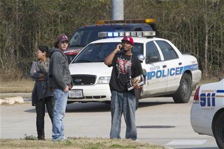 Students talk on cell phones and wait after evacuating on foot from the Lone Star College North Harris campus in Houston, Texas, January 22, 2013. REUTERS/Richard Carson
