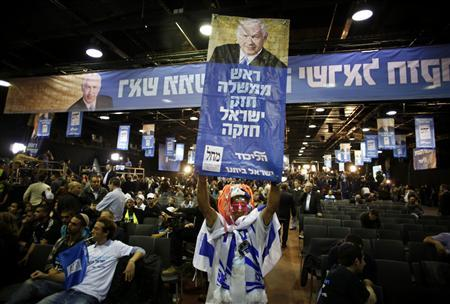 A supporter of the Likud party holds up a campaign banner depicting Prime Minister Benjamin Netanyahu as he celebrates after the exit polls were announced at the party's headquarters in Tel Aviv January 22, 2013. REUTERS/Baz Ratner (ISRAEL - Tags: POLITICS ELECTIONS)