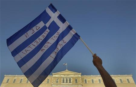 A protester waves a Greek flag during a rally against austerity economic measures and corruption in front of the parliament in Athens' Constitution (Syntagma) square June 19, 2011. REUTERS/Yiorgos Karahalis