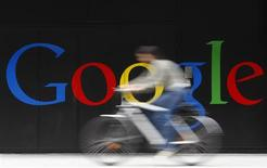 An employee rides her bike past a logo next to the main entrance of the Google building in Zurich in this July 9, 2009 file photo. REUTERS/Christian Hartmann/Files