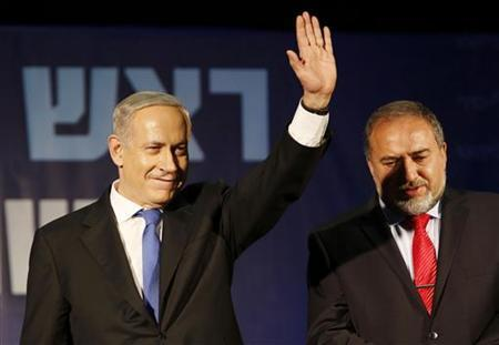 Israel's Prime Minister Benjamin Netanyahu waves to supporters as he stands next to former foreign minister Avigdor Lieberman at the Likud party headquarters in Tel Aviv January 23, 2013. REUTERS/Baz Ratner