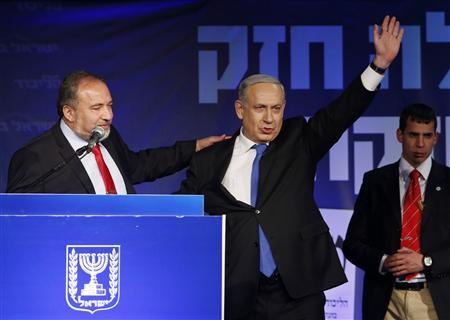 Israel's Prime Minister Benjamin Netanyahu (C) waves to supporters as he stands next to former foreign minister Avigdor Lieberman (L) at the Likud party headquarters in Tel Aviv January 23, 2013. Hawkish Prime Minister Netanyahu emerged the bruised winner of Israel's election on Tuesday, claiming victory despite unexpected losses to resurgent centre-left challengers. REUTERS/Baz Ratner (ISRAEL - Tags: POLITICS ELECTIONS)