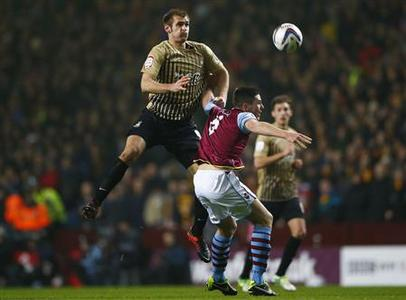 Aston Villa's Ciaran Clark challenges Bradford City's James Hanson (L) during their English League Cup semi-final second leg soccer match at Villa Park in Birmingham, central England, January 22, 2013. REUTERS/Darren Staples