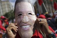 Um partidário do presidente venezuelano Hugo Chávez veste uma máscara representando Chávez em comício em Caracas. Chávez está sendo submetido a fisioterapia em Cuba para poder voltar a seu país, depois de ficar fora um mês e meio recuperando-se de uma complexa cirurgia contra um câncer, disse nesta terça-feira seu colega boliviano, Evo Morales. 10/01/2013 REUTERS/Gil Montano