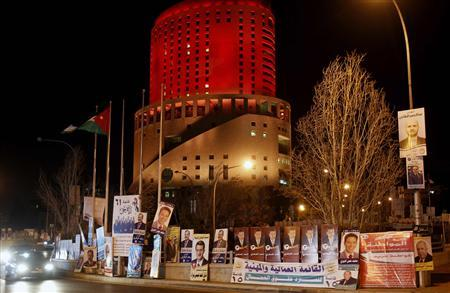Cars drive past parliamentary election campaign posters in central Amman January 22, 2013. REUTERS/Ali Jarekji